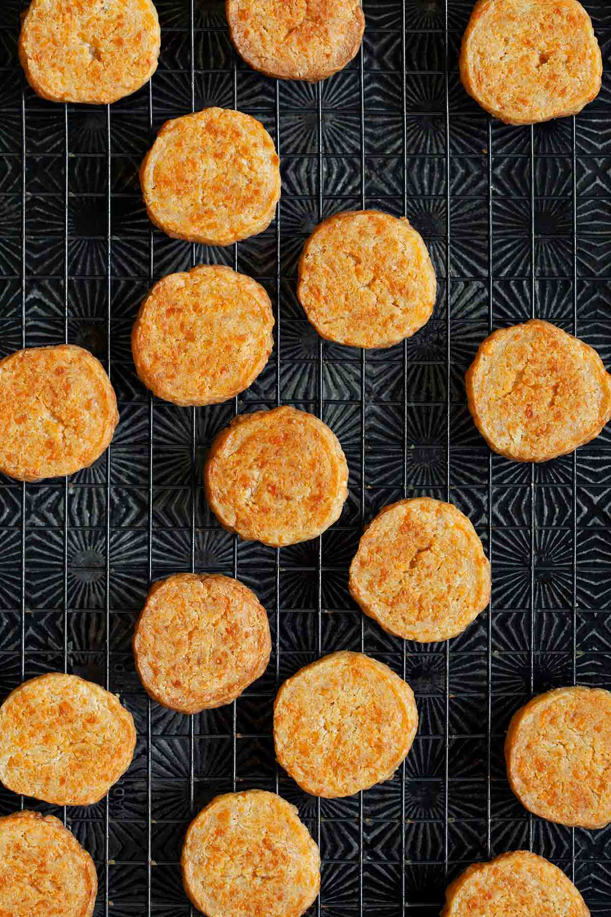 Cheddar-Parmesan crackers on a black wire rack.