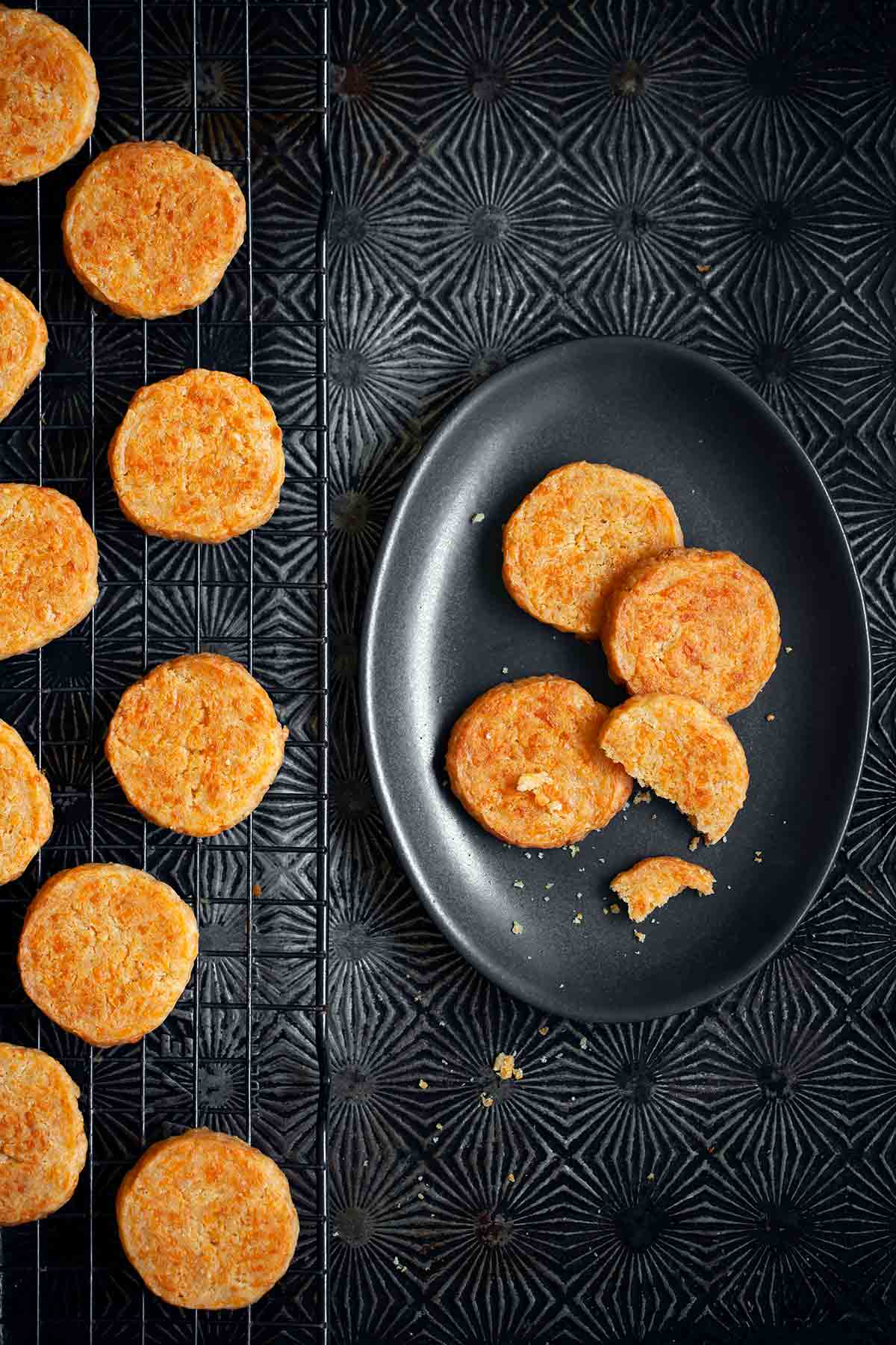 Cheddar-Parmesan crackers on a black wire rack with a few on a black oval plate beside the rack.