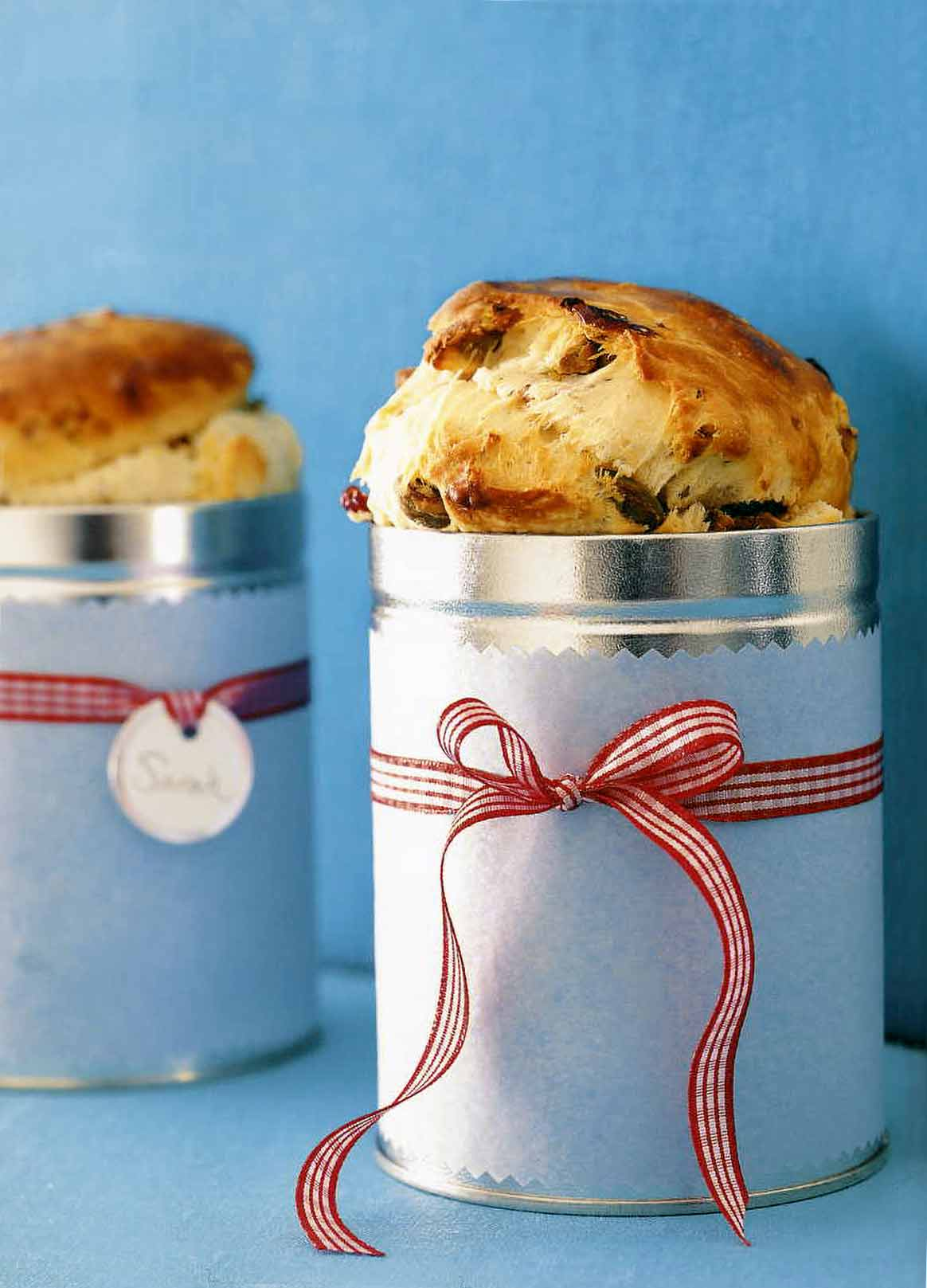 Two cranberry panettone breads baked in tins, wrapped in white paper and tired with red ribbon