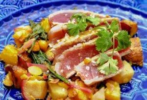 Three sliced of maple-glazed tuna with pear-potato salad around it on a blue plate