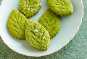 White plate with five green leaf-shaped cookies with coarse sugar on top