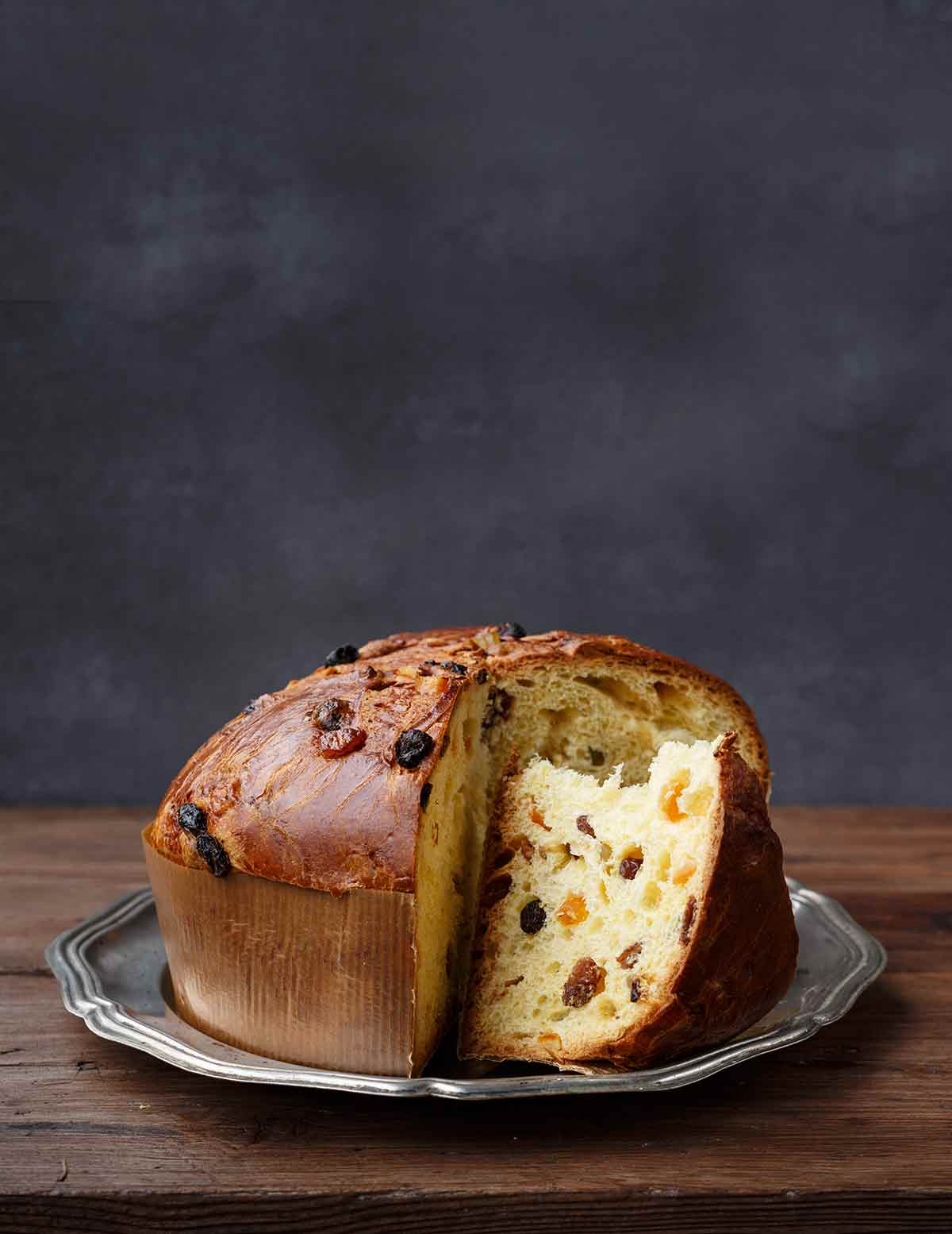 A panettone studded with dried fruit on a silver platter with a couple of wedges cut from it.