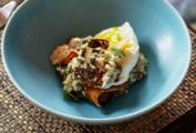 Blue bowl of wild mushroom grits topped with an egg, parmesan cheese, and basil