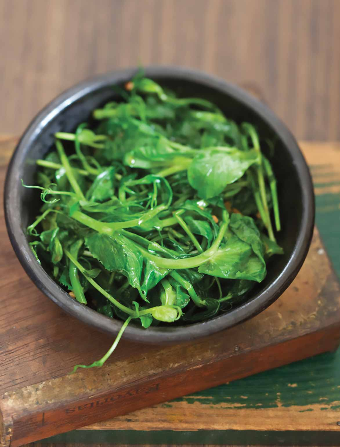 A brown bowl filled with stir-fried pea shoots