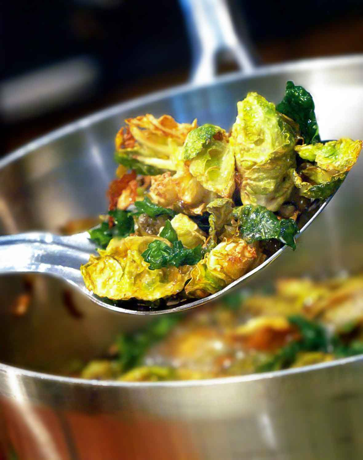A serving spoon of fried Brussels sprouts with walnuts and capers resting over a large metal bowl.