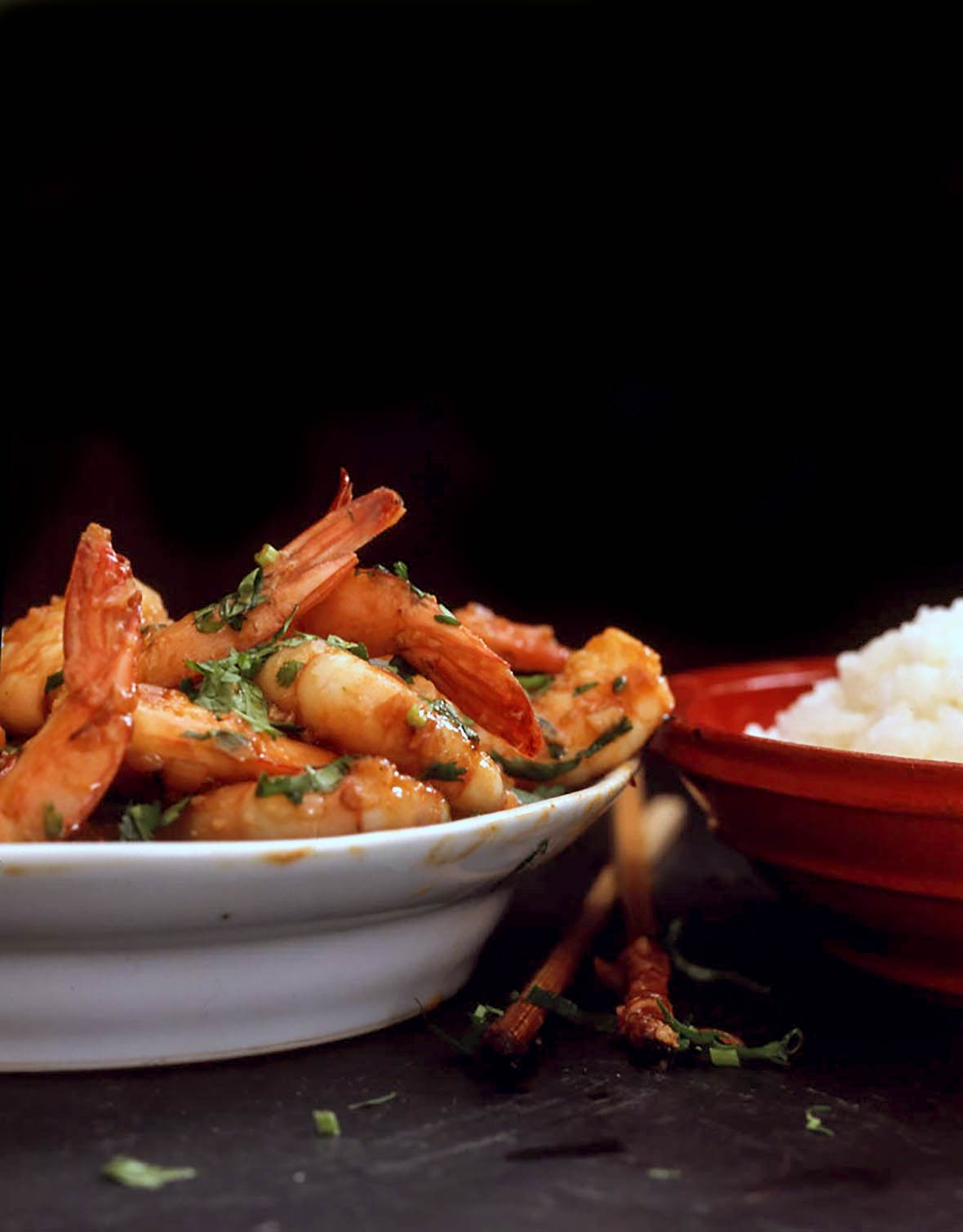 A white bowl piled with spicy shrimp and a red bowl of white rice
