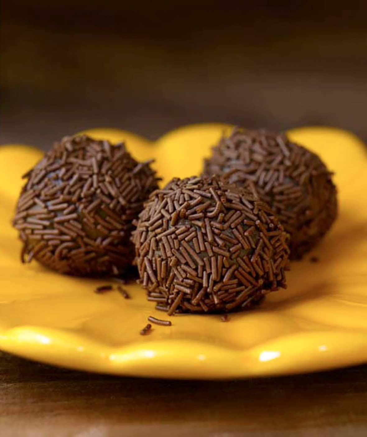 Three golf-ball size chocolate Brazilian candies covered with chocolate sprinkles on a yellow plate