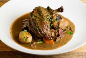 Julia Child's coq au vin in a white bowl with onions, carrots, bacon, and gravy.