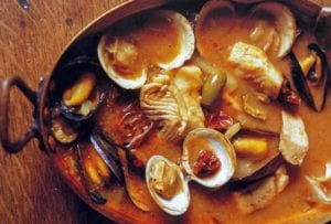 Copper pot with seafood soup with fish fillets, clams, mussels, olives, tomato broth