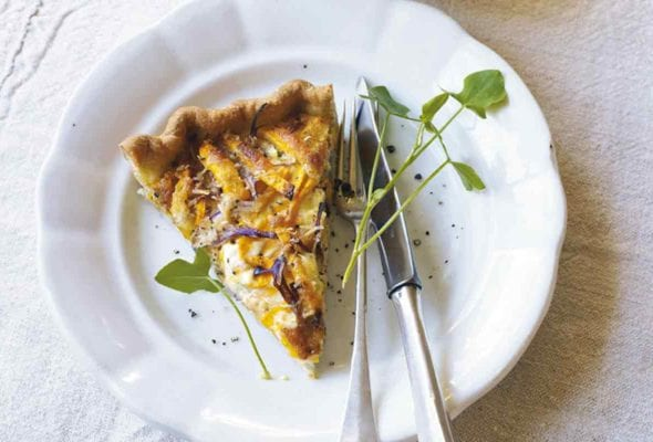 A slice of butternut squash and Parmesan tart on a white plate with a fork and knife, garnished with microgreens.