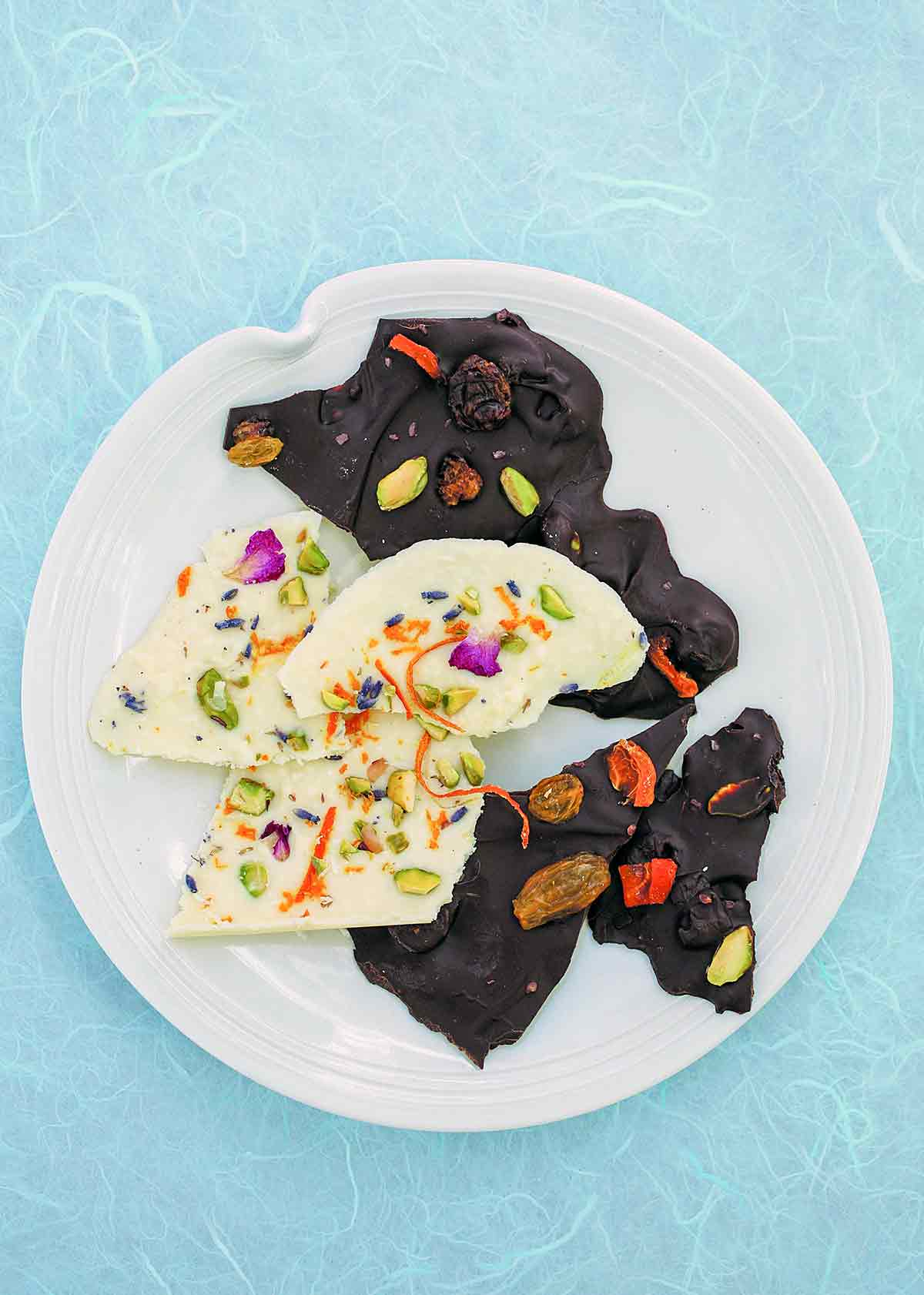 Several pieces of chocolate bark with apricots and pistachios on a white plate with a blue background.