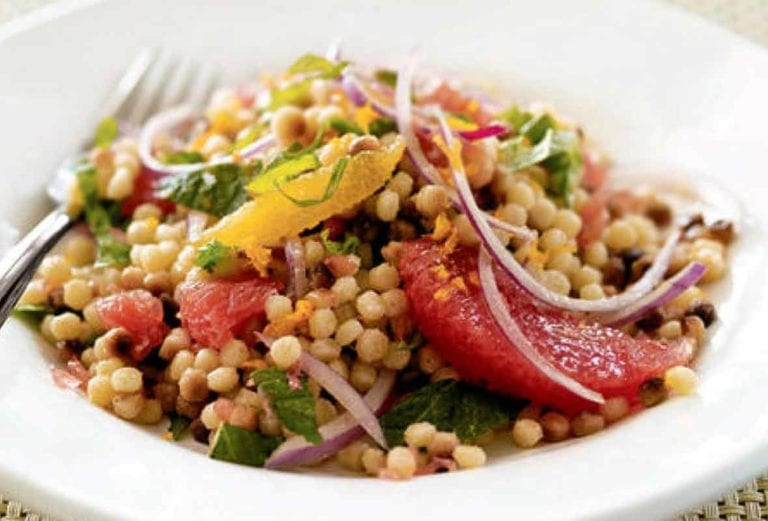 A white bowl filled with fregola salad with fresh citrus and red onion and mint leaves on a woven placemat.
