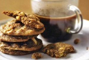 A stack of hazelnut espresso cookies next to a mug of coffee.