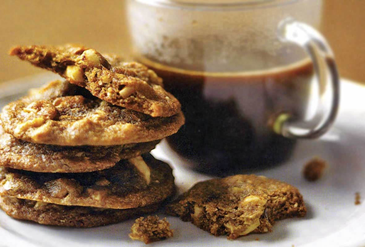 A stack of hazelnut espresso cookies next to a mug of coffee.