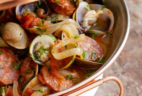 A cataplana with slices of spicy chouriço sausage and sweet clams in a tomato-onion broth