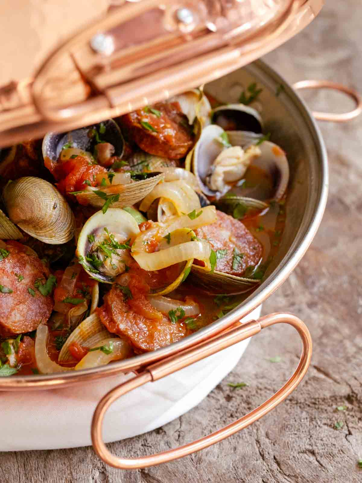A cataplana with slices of spicy chouriço sausage and sweet clams in a tomato-onion broth.