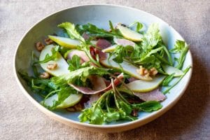 An arugula salad with country ham, pears, and honey vinaigrette, topped with chopped walnuts in a white bowl.