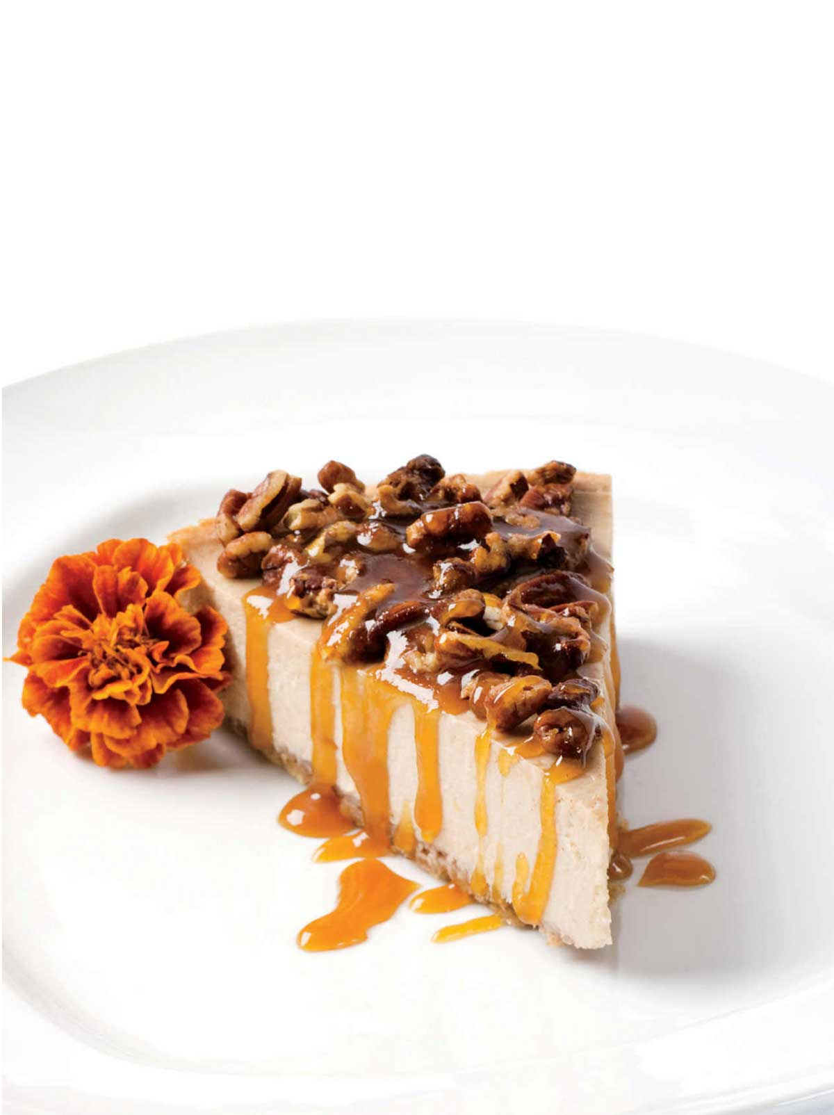 A slice of banana rum cheesecake with maple rum sauce and pecan pieces on top and a marigold beside the cake.