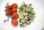 A white plate with a mound of cannellini bean salad and a bunch of grape tomatoes on the vine.