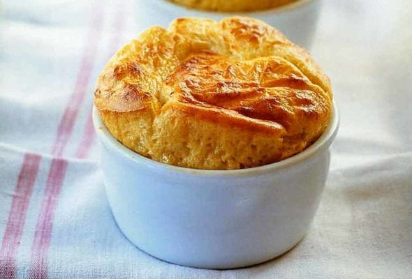 Two puffy, golden Parmesan and Gruyere Cheese Souffles in white bowls on a towel