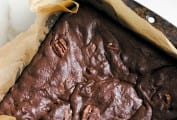 A parchment-lined square pan filled with pecan-studded best brownies.