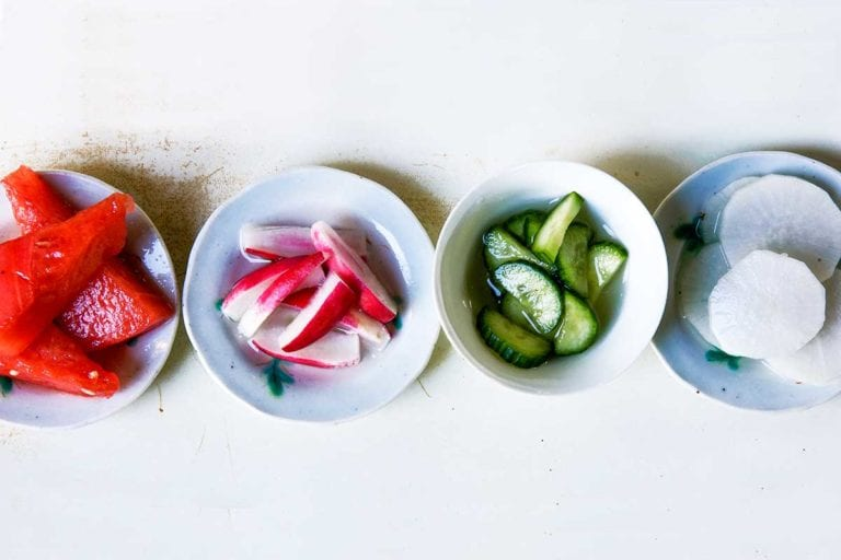 Four bowls of salt and sugar pickles; one with watermelon, one with red radish, one with cucumber, and one with daikon radish.