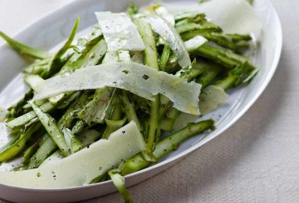Two plates of shaved asparagus and pecorino salad on a tablecloth