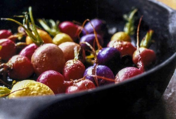 Black skillet with red, white, yellow, and purple roasted radishes