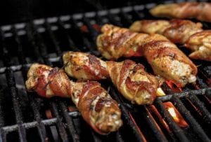 Bacon-wrapped chicken wings, secured with toothpicks on an open grill.