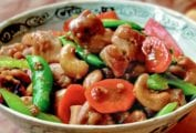 Bowl of cashew chicken with chunks of stir-fried chicken, carrots, sugar snap peas, celery, cashews