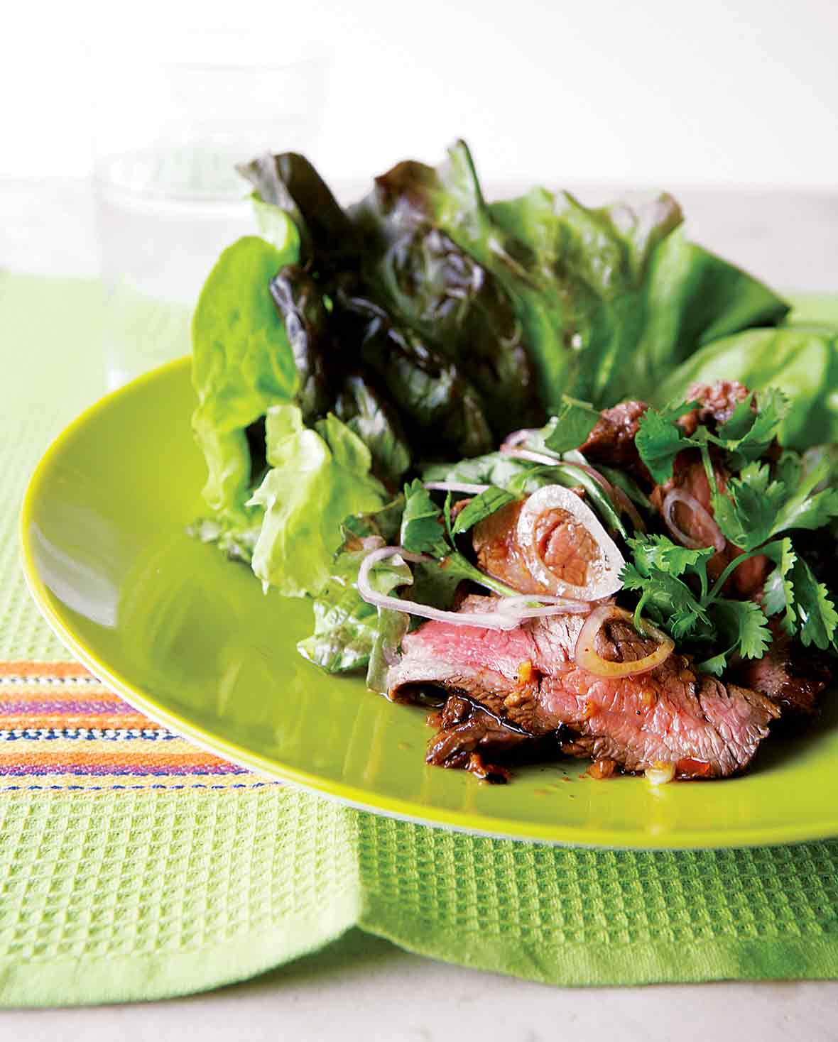 A green plate topped with a grilled Thai beef salad made with lettuce, beef, shallots, and cilantro.