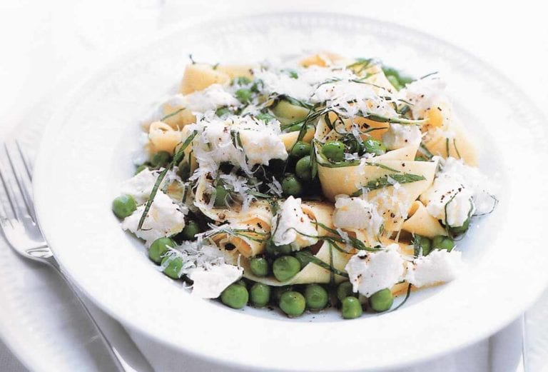 A white bowl filled with lemon, ricotta, and pea pasta.