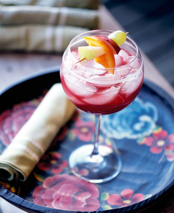 A wine glass filled with ruby sangria, ice, and a fruit skewer on a floral-patterned serving tray.