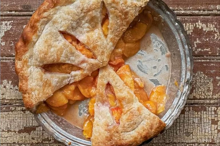 A baked fresh peach pie with three slices missing.