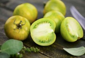 Four whole and one halved green tomato with a sprig of thyme and a couple of sage leaves to be used in the corn and green tomato salad.