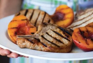 A woman holding a white platter of grilled country pork chops with grilled peaches.