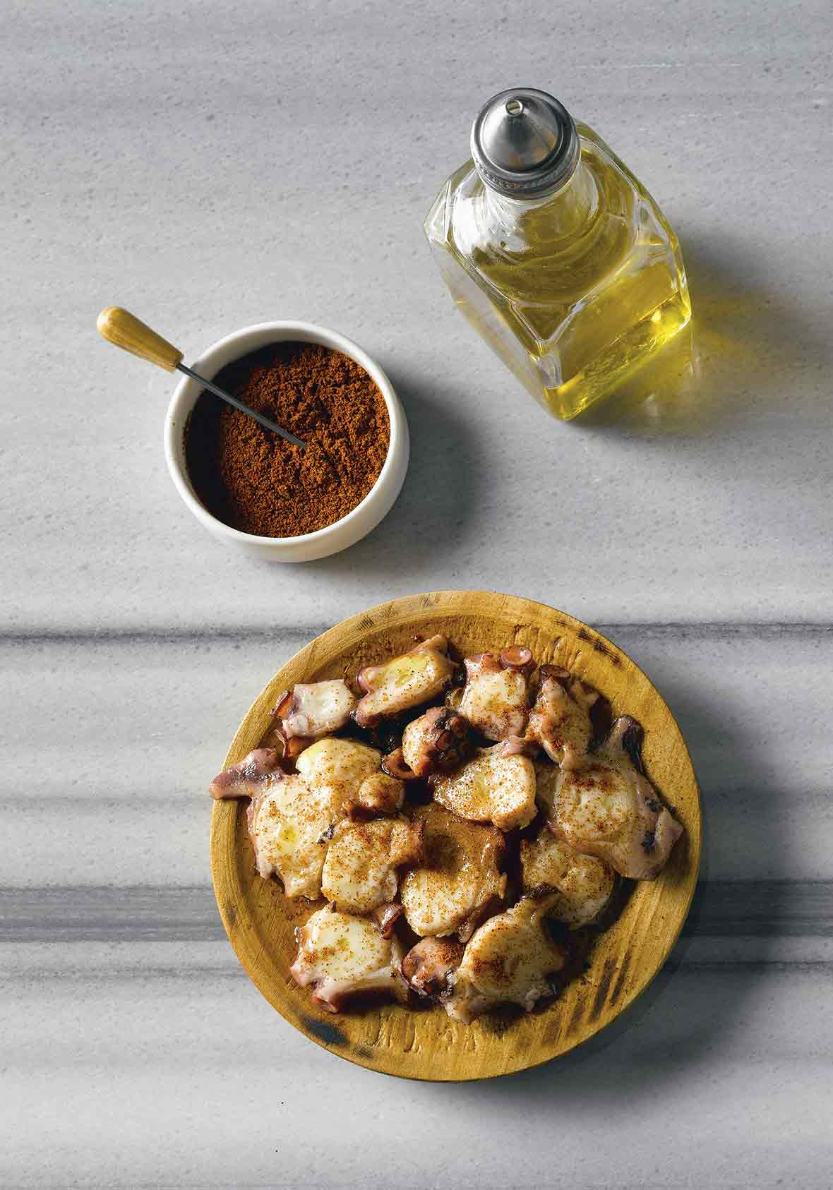 Wooden bowl of octopus with paprika, bowl of paprika, cruet of olive oil