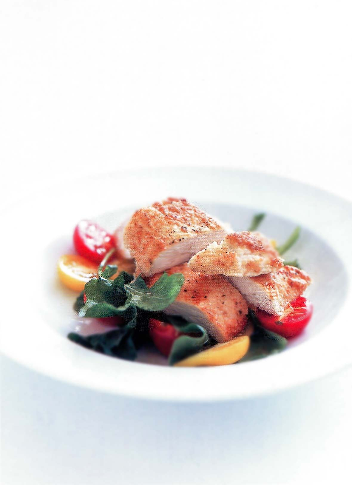White bowl of sliced parmesan-crusted chicken, lettuce, and red and yellow cherry tomatoes
