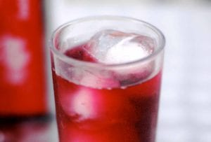 Tall glass of tinto de verano, a read wine with Sprite, and ice cubes