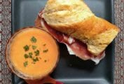 A square grey plate containing a bowl of cantaloup soup and a prosciutto mozzarella sandwich on a baguette.