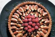 A fresh fig and raspberry tart drizzled with honey on a black platter.