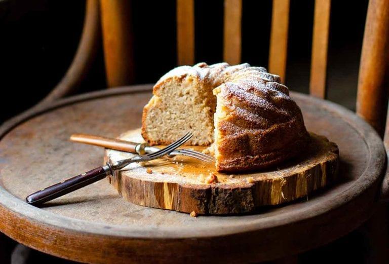 A partially cut St. Phanourios cake on a wooden slab on a wooden chair.