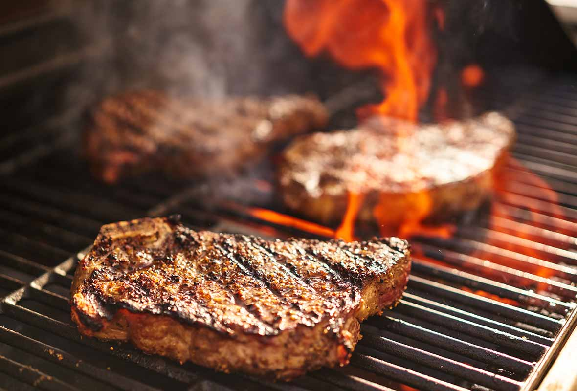 Two steaks on a grill with fire flaring up