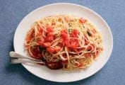 An oval platter topped with a tangle of spaghetti and raw tomatoes with a fork and spoon resting in the pasta.