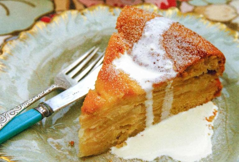A decorative plate topped with a slice of drunken apple cake that is drizzled with cream.