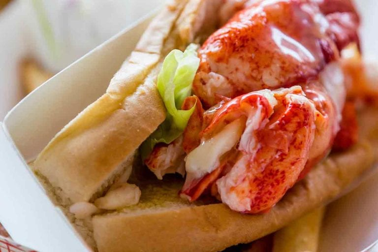 A lobster roll in a cardboard sleeve with a little lettuce and a lemon wedge in the background.