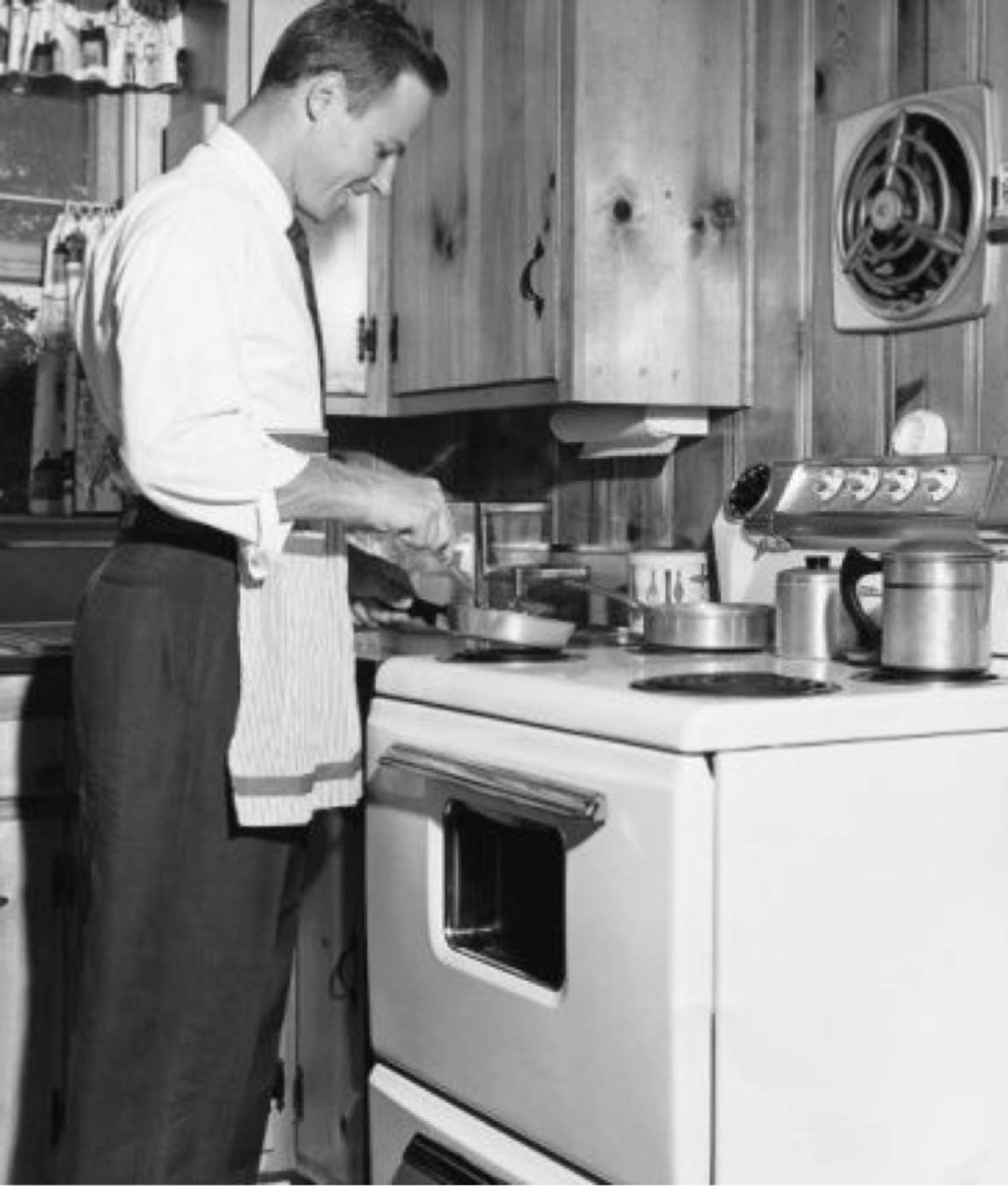 Vintage photo of a man in slacks and apron cooking at a stove