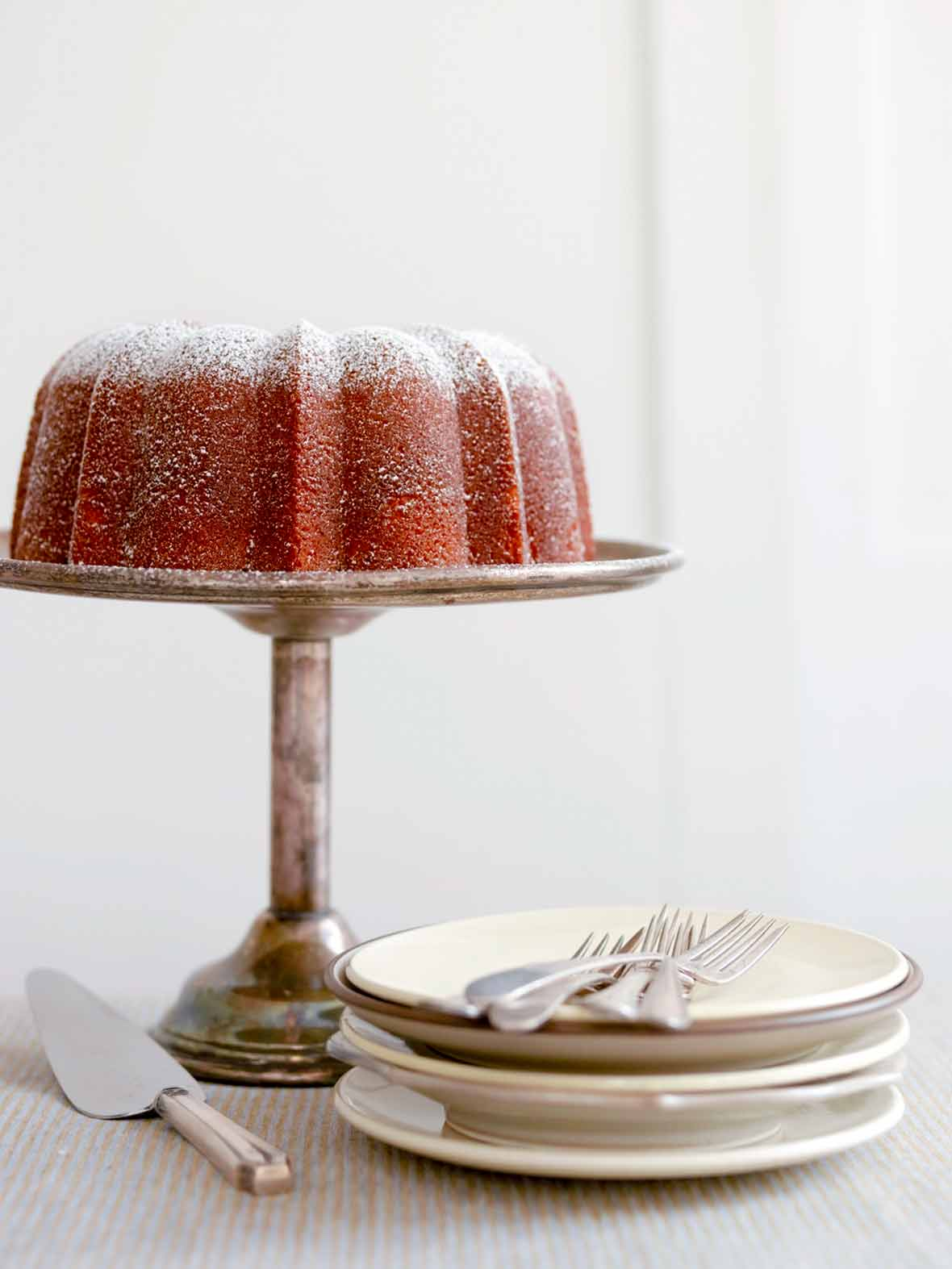 A Portuguese orange olive oil cake, dusted with confectioners' sugar on a silver cake stand.