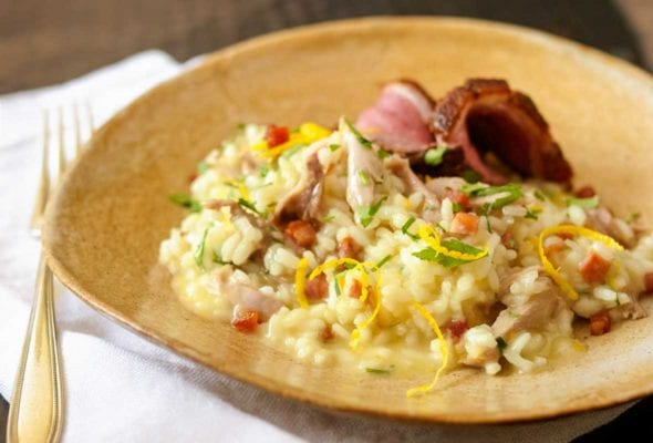 A wide ceramic bowl filled with Portuguese duck risotto, topped with orange zest and parsley.