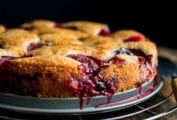 A purple plum torte with dripping juice on a baking pan, all on a cooling wrap